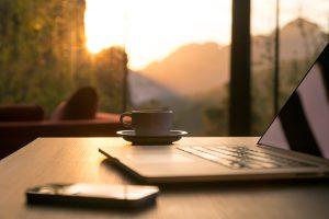 Nomad work Concept Image Computer Coffee Mug and Telephone large windows and sun rising, focus on coffee mug